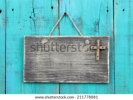 Blank weathered sign with wooden cross hanging by rope on antique teal blue wood door - stock photo