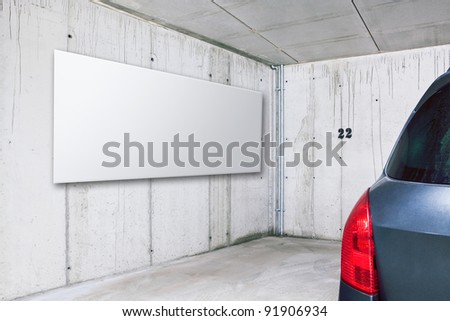 Blank white advertisement board on the wall in public parking area space - stock photo
