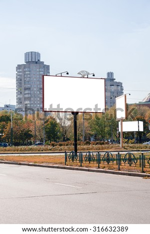 Blank white advertising banners near the road in autumn. Put your text or images inside