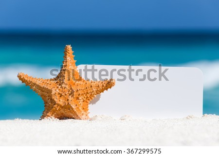 Blank white board and starfish on sand against turquoise caribbean sea water. Tropical summer vacation concept  - stock photo