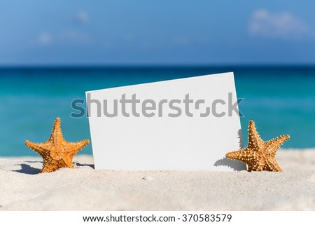 Blank white board and two starfishes on sand against turquoise caribbean sea water. Tropical summer vacation concept - stock photo