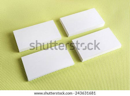 Blank white business cards on a green background. Template for branding identity. - stock photo