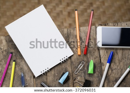 Blank white calendar and smartphone on wooden old dirty texture border table with school supply - stock photo