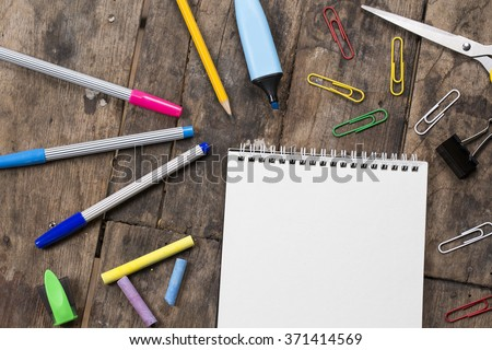 Blank white calendar paper on vintage wood table with color pen, pencil and accessories - stock photo