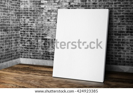 Blank white canvas frame leaning at grunge brick wall and wood floor, Mock up template for adding your design.