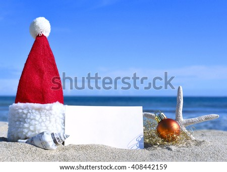 Blank white card with christmas decoration and sea shell on a tropical beach. Christmas holidays. Greeting card with copy space on the beach.  - stock photo