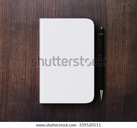 Blank white diary cover and pen on brown wooden table, mock up - stock photo