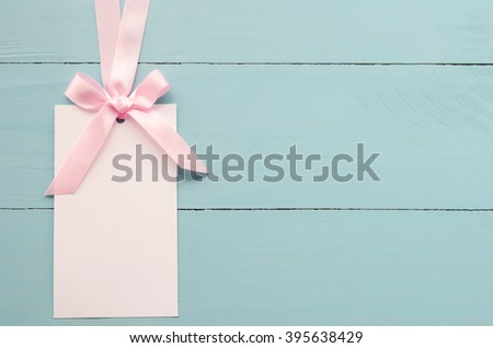 Blank white greeting card with pink ribbon on blue wooden background with soft vintage tone - stock photo