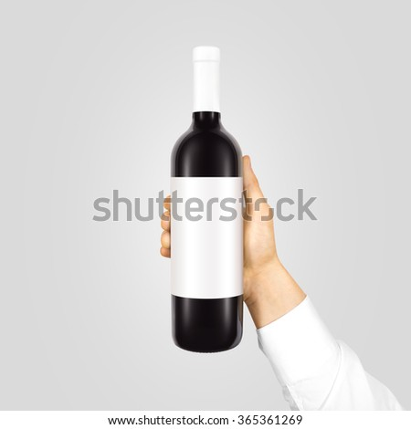 Blank white label mock up on black bottle of red wine in hand isolated. Alcohol bottle mockup presentation ready for logo design. Full drink bottle holder template empty sticker. Clear tag vine bottle - stock photo