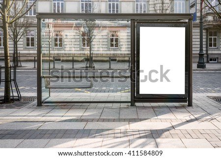 Blank white mockup of bus stop vertical billboard in front of empty street background - stock photo