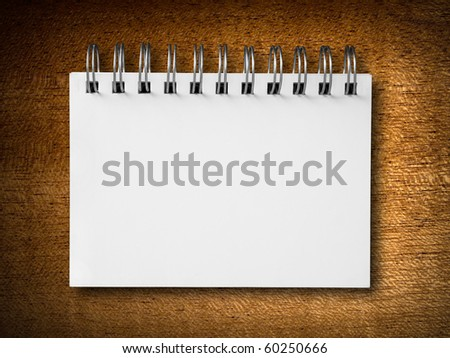 blank white notebook on wood background