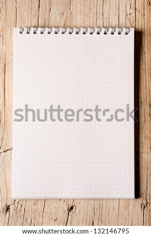 Blank white notepad on a hardwood floor lit on the side - stock photo