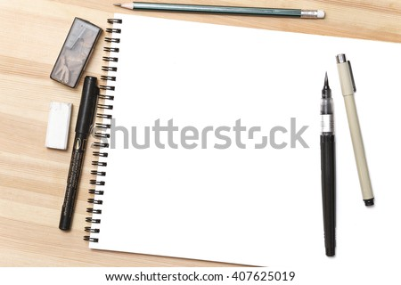 Blank white notepad with pens on wooden table - stock photo