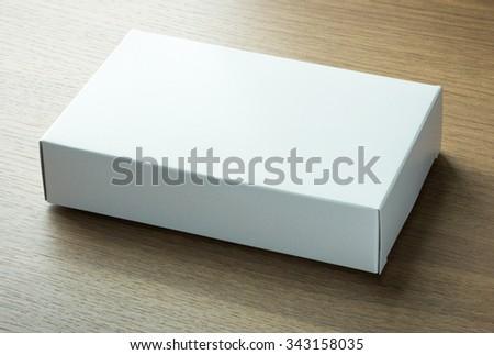 blank white paper box on dark wood background - stock photo