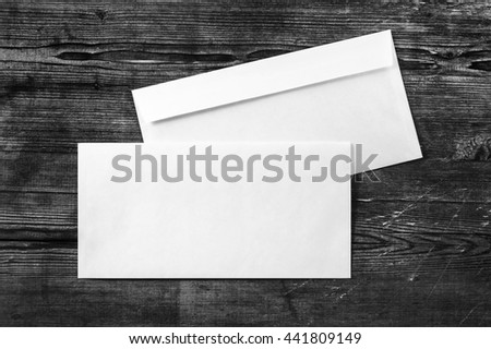 Blank white paper envelopes. template. Photo of blank envelopes on dark wooden background. Two envelopes. Back and front view. Template for ID. Top view. - stock photo