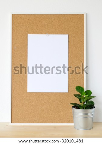 Blank white paper on cork board and little tree on wood floor over white cement wall background, template - stock photo