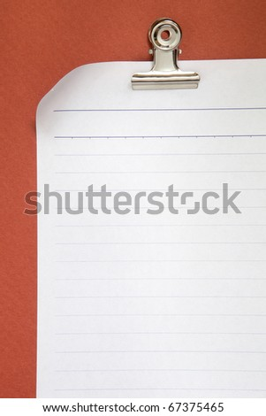 blank white paper on red background with clip - stock photo