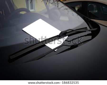 Blank white paper under the windshield wipers. - stock photo