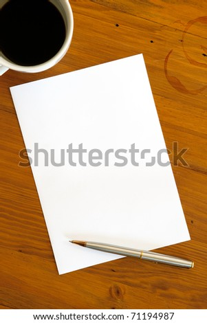 Blank white paper with pen and a half-empty cup of coffee, over coffee-stained timber desk.  Ready for your message. - stock photo