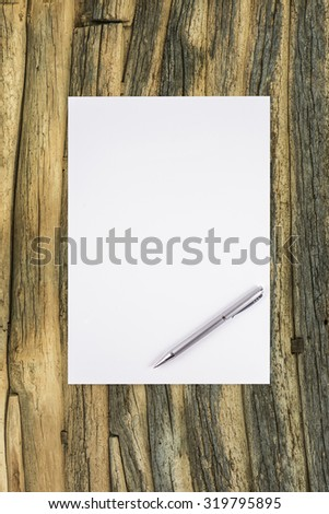 Blank white paper with pen on a wooden desk. - stock photo