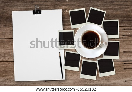 blank white paper with photo frame and coffee cup on wooden background - stock photo