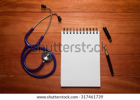 blank white paper with stethoscope and black ink pen on wooden table, can be refilled with words  - stock photo