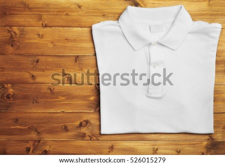 Blank white polo shirt on wooden background