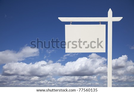 Blank White Real Estate Sign Over Clouds and Sky Ready For Your Own Message. - stock photo