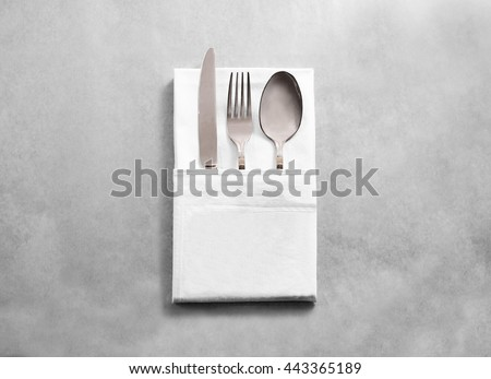 Blank white restaurant cloth napkin mockup with silver cutlery set, isolated. Knife fork and spoon in clear textile towel mock up template. Cafe branding identity clean napkin surface for logo design. - stock photo
