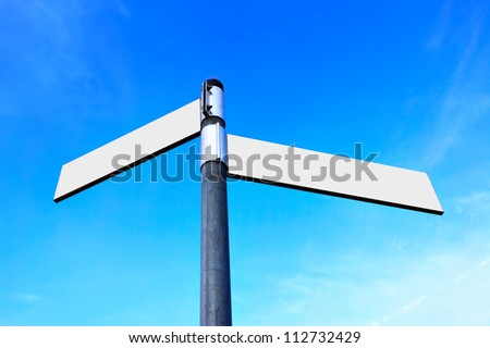 Blank white road signs over blue sky - stock photo