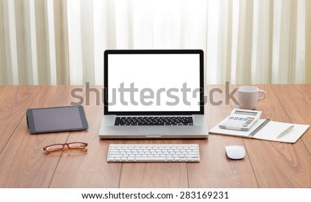 Blank white screen laptop computer on wooden floor - stock photo