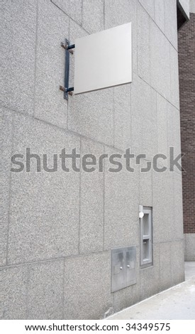 blank white sign on a stone wall