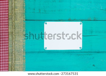 Blank white sign on antique teal blue wood background with red and white gingham, burlap and rope border - stock photo