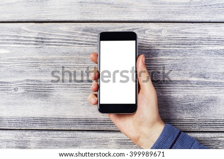 Blank white smartphone held by male hand on wooden background. Mock up - stock photo