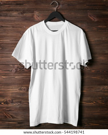 Blank white t-shirt against wooden background