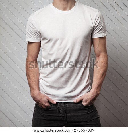 blank white t-shirt on muscle young man and white wall made of wood - stock photo
