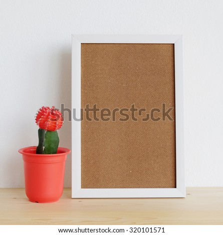 Blank white wooden frame and cactus on wood board over white cement wall background, template ,mock up - stock photo