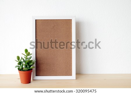 Blank white wooden frame and tree on wood board over white cement wall background, template ,mock up - stock photo