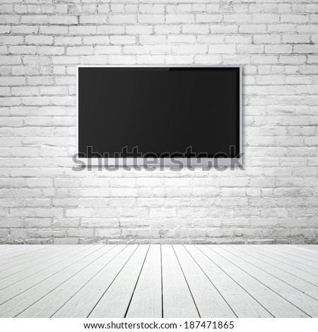 blank wide screen TV on brick wall in room - stock photo