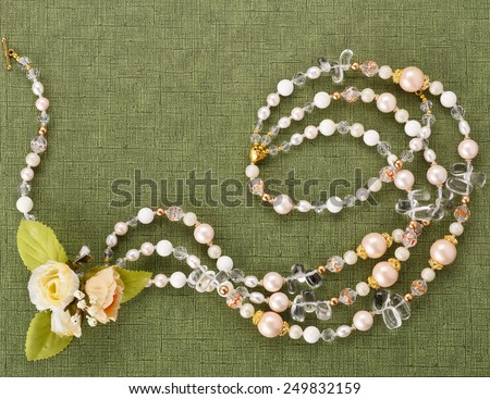 Blank with a necklace and flowers on green background - stock photo