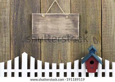 Blank wood sign over white picket fence with birdhouse - stock photo