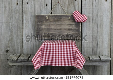 Blank wood sign with heart by picnic table with red gingham tablecloth - stock photo