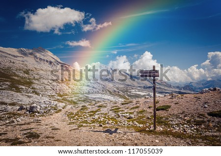Blank wooden arrow sign with rainbow and mountain scenery - stock photo