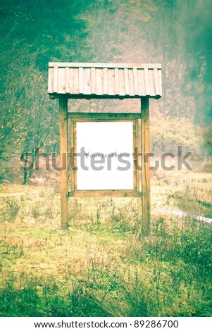 Blank wooden billboard with copy space in front of the forest - stock photo