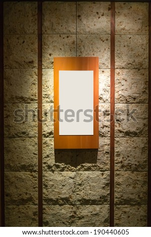 Blank wooden frame on stone wall illuminated spotlights in interior room - stock photo