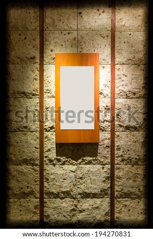 Blank wooden frame on stone wall illuminated spotlights in interior room (with strong vignette) - stock photo