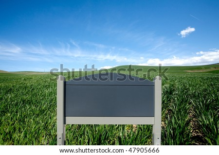 Blank wooden sign Against green field and blue sky - stock photo