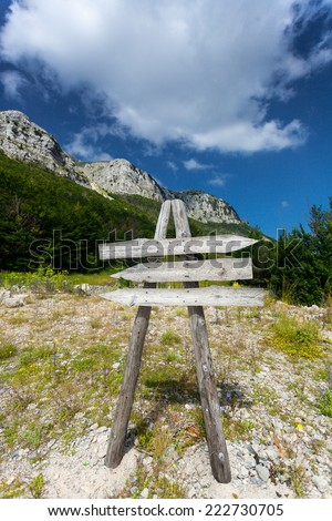 Blank wooden signpost on path to high mountain - stock photo