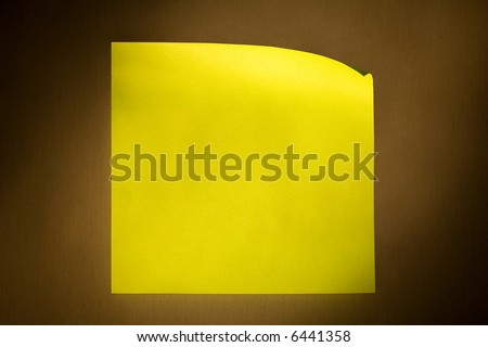 Blank yellow adhesive post-it note stuck on stainless steel surface of refrigerator in warm yellow illuminating cone. - stock photo