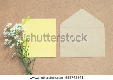blank yellow note for your text or quote with envelope and  white  flower bouquet